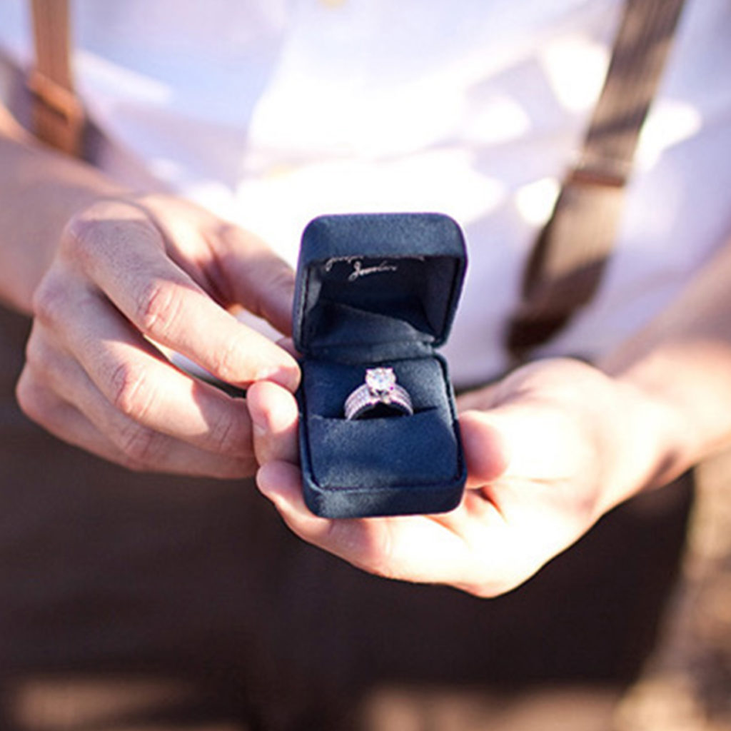 Uomo con anello in mano che propone un anello