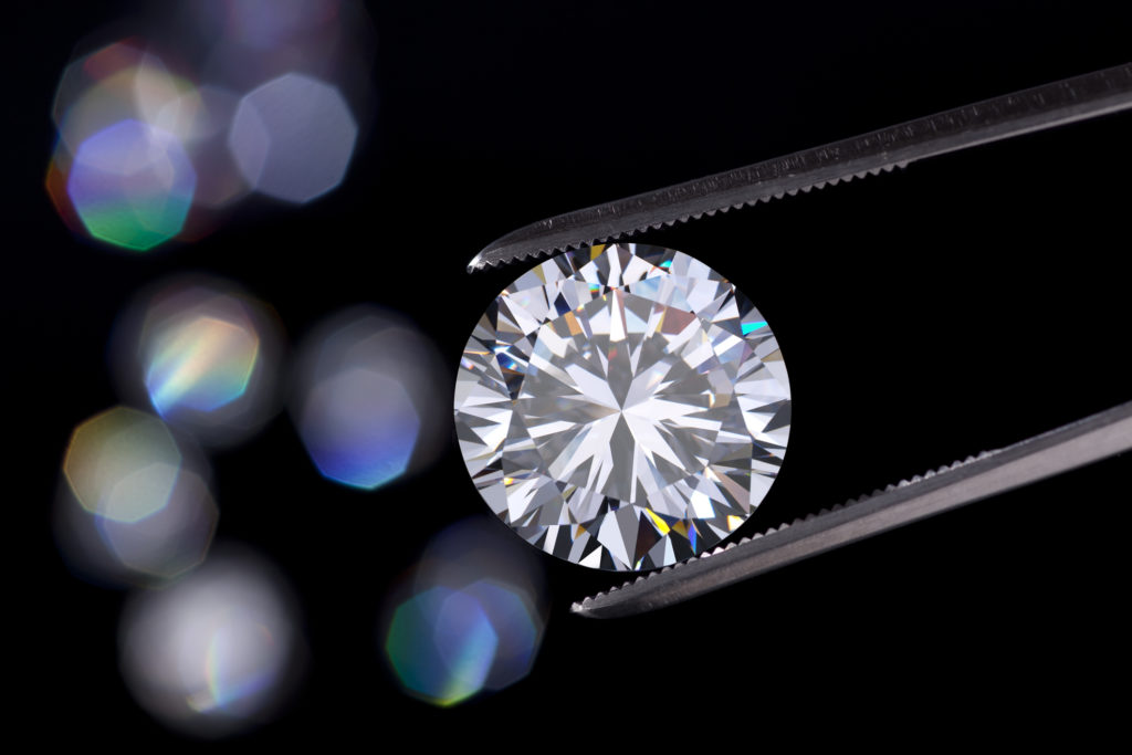 Un diamante con forma del taglio rotondo a brillante tenuto da pinzette da gioielleria