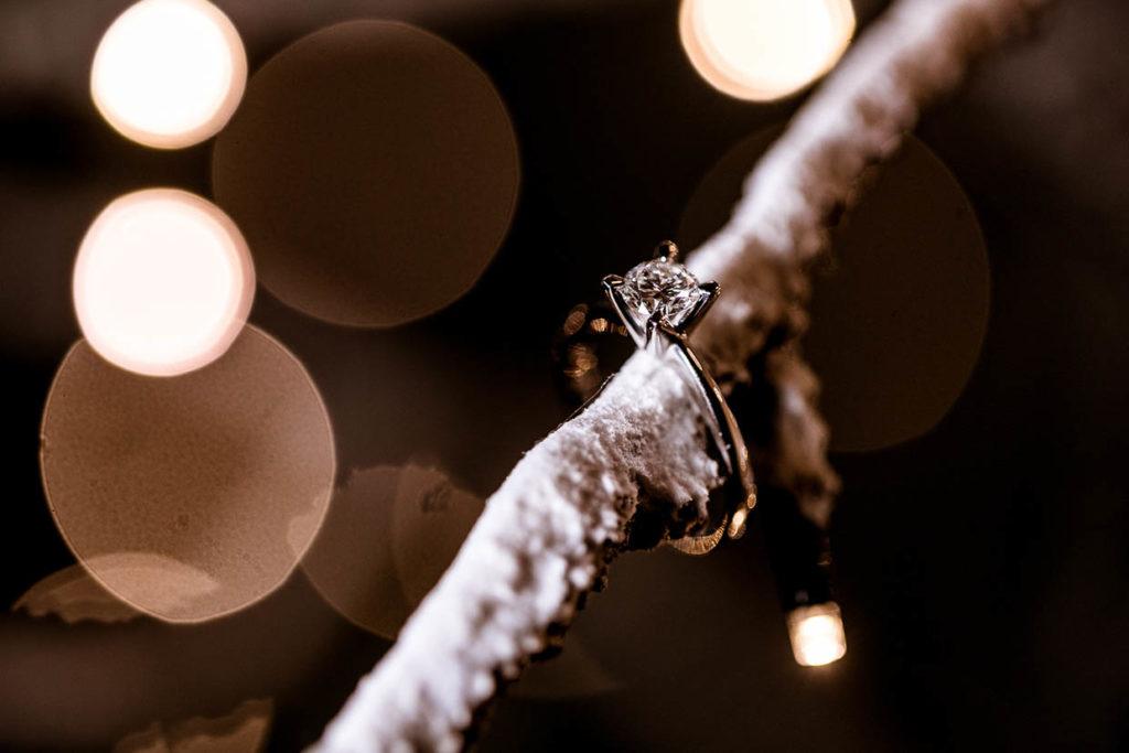 Anello solitario con diamante inserito in un ramo di un albero innevato