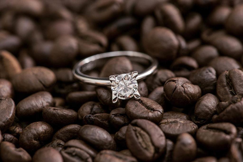 Anello della guida come scegliere un anello di fidanzamento, adagiato su chicchi di caffè