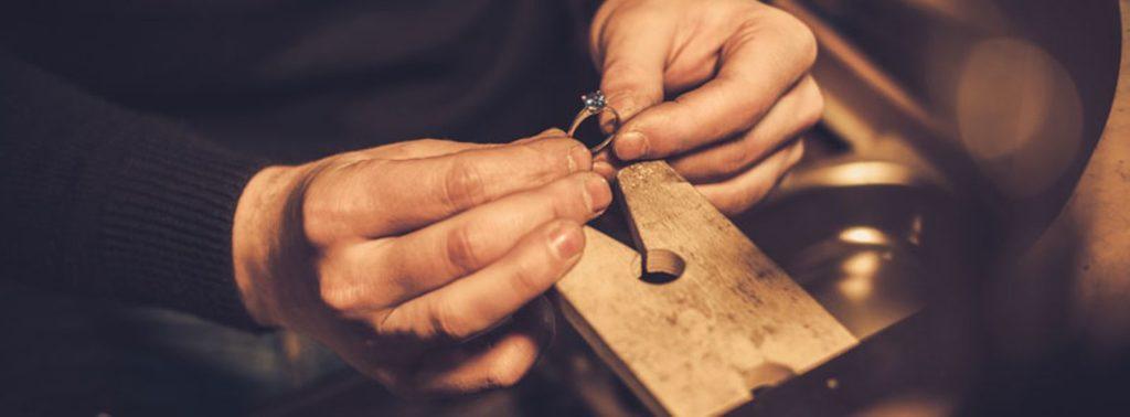 Mani di un'orafo al banchetto di lavoro con un anello in mano